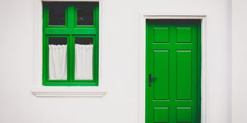 Green door and window on white house